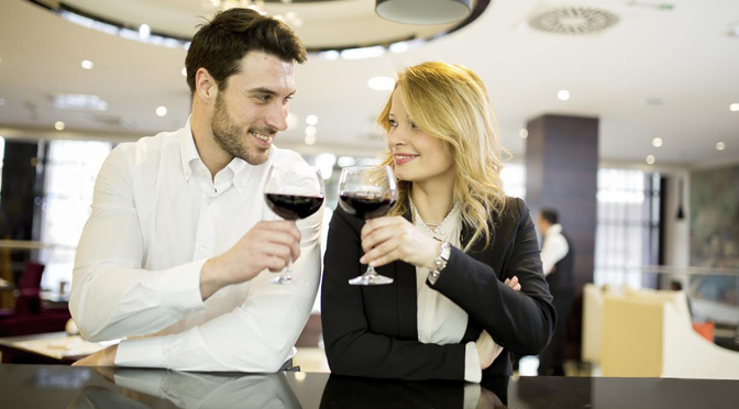 Business couple with wine at bar